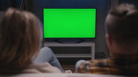 Family Couple Watches Green Screen TV Mockup Sitting on Couch in Living Room Together. Rear View on Casual People who Watching TV Green Screen in Domestic Cinema. Looking TV Show or News in Home Rest
