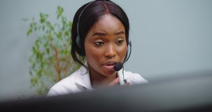 Close up of african female doctor wear headset make online video call consult patient. Afro american black woman therapist videoconferencing talking to camera in remote chat. Telemedicine, telehealth.