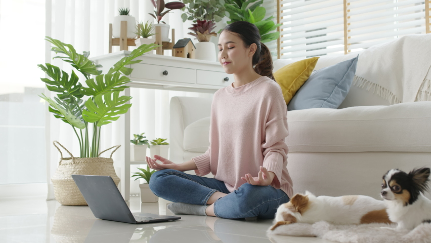 Attractive beautiful young asia female close eyes maditate at home self break stress relief from work, stay quarantine social distance in online yoga class community, wellness wellbeing lifestyle. Royalty-Free Stock Footage #1066233253