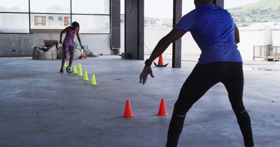 African american woman doing slalom with a football in urban building with man cheering her. urban fitness and healthy lifestyle. | Shutterstock HD Video #1066233643