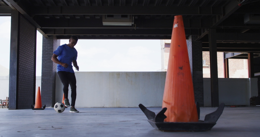 African american man doing tricks with a football in an empty urban building. urban fitness and healthy lifestyle. | Shutterstock HD Video #1066233679