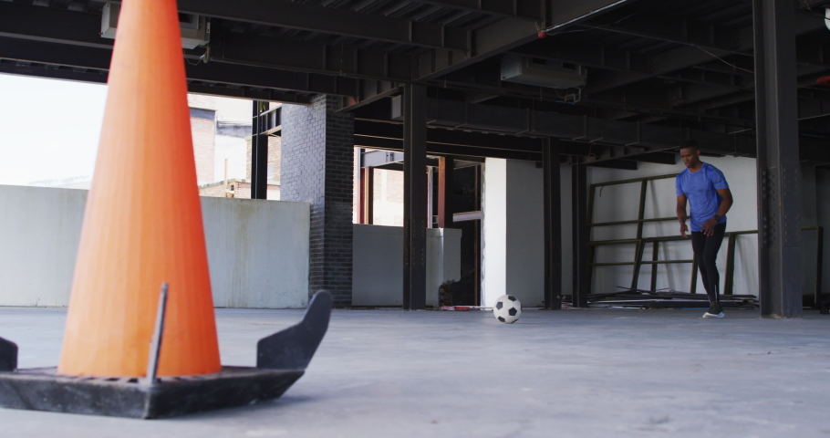 African american man kicking a football in an empty urban building. urban fitness and healthy lifestyle. | Shutterstock HD Video #1066233694