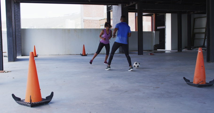 African american man and woman playing football in an empty urban building. urban fitness and healthy lifestyle. | Shutterstock HD Video #1066233745
