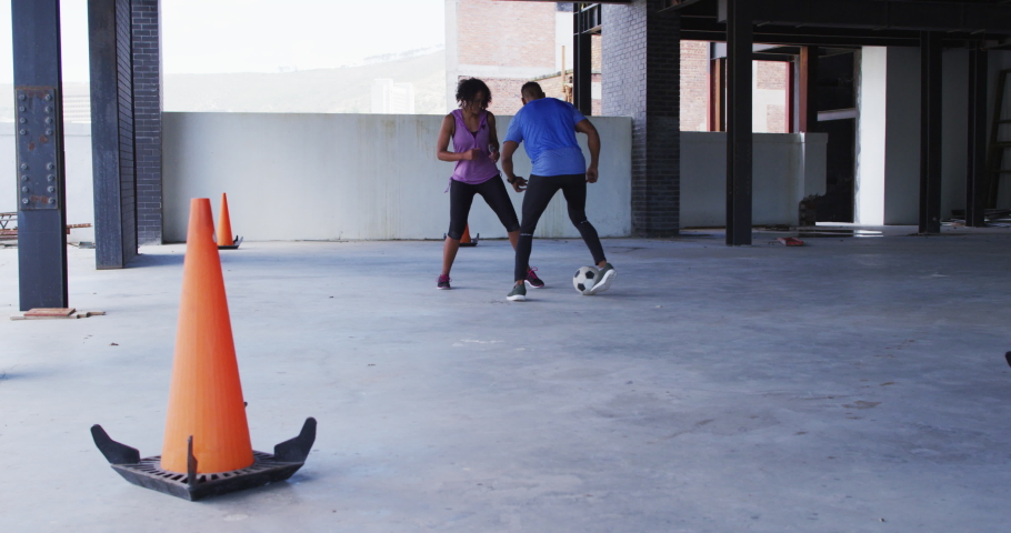 African american man and woman playing football in an empty urban building. urban fitness and healthy lifestyle. | Shutterstock HD Video #1066233850