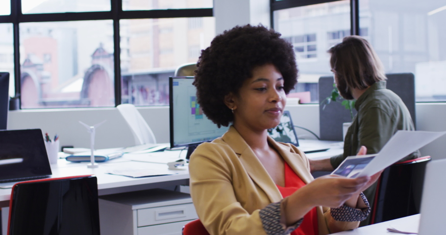 Mixed race businesswoman sitting using a laptop going through paperwork in modern office. coworkers in the background. business modern office workplace technology. | Shutterstock HD Video #1066236073