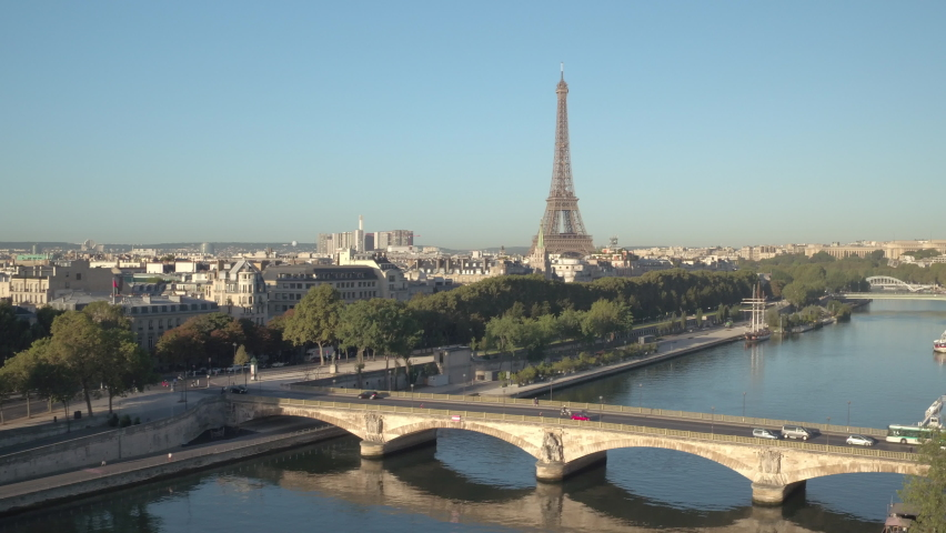 Aerial elevation from the docks of the Seine river in Paris toward the Eiffel Tower at sunrise, bridge with traffic in front. Ending view on the Eiffel tower in the middle of Paris cityscape, 4K