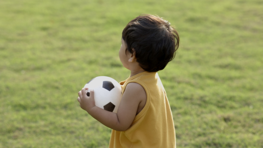 Asian Little boy wear a yellow shirt and play a football in the middle of the lawn. | Shutterstock HD Video #1066248646