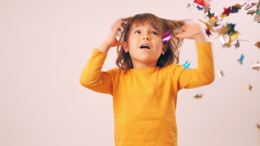 Cute happy child is celebrating a birthday, having fun and catching confetti from a firecracker with his hands. Isolate on a white background | Shutterstock HD Video #1066249888