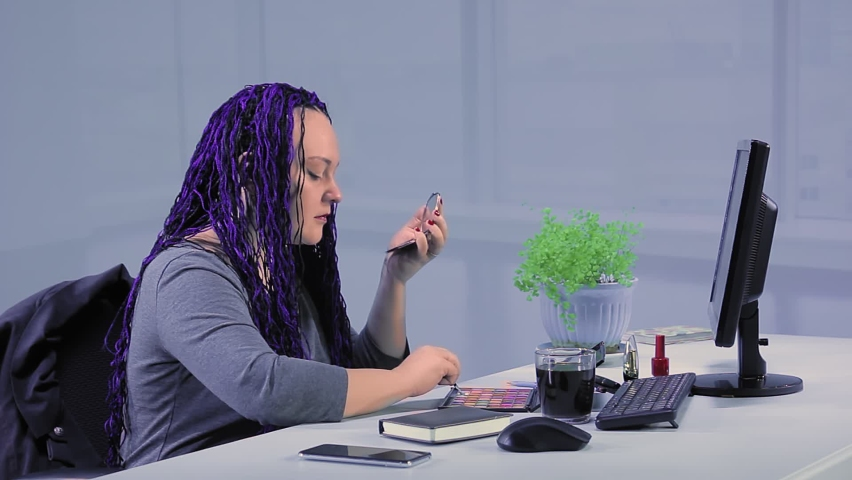 A woman with blue afro braids at work in the office paints her eyes with shadows | Shutterstock HD Video #1066253662