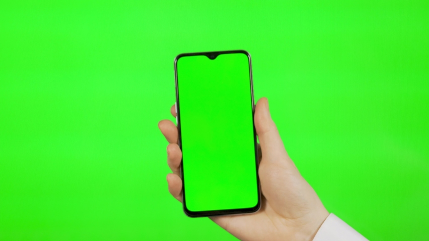 The Businessman's Hand Holds a Blank Mobile Phone with Green Screen, Green Background Vertical on Green Background, Alpha Channel, Chroma key, Mockup. The Person Uses the Smartphone. | Shutterstock HD Video #1066254784