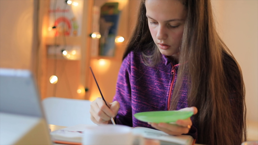 Young girl drawing with brush on paper and looking lesson on the tablet. Online education concept | Shutterstock HD Video #1066257538
