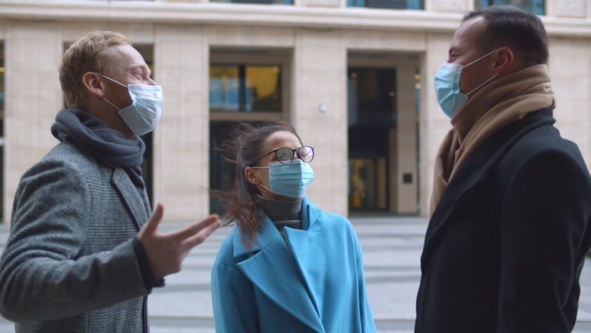 Coworkers in protective face masks elbow bumping greeting outdoors. Young elegant business people wearing safety mask doing elbow bump meeting outside business center Royalty-Free Stock Footage #1066262365