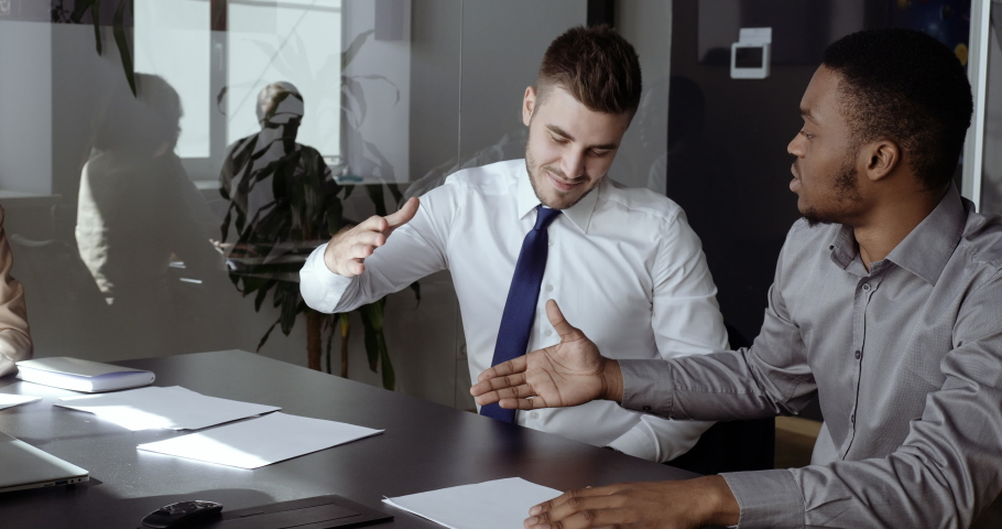 Confident caucasian male financial advisor bank worker broker explaining deal benefits, speak about business to focused african american man, shaking hands after making agreement in office conference | Shutterstock HD Video #1066264807