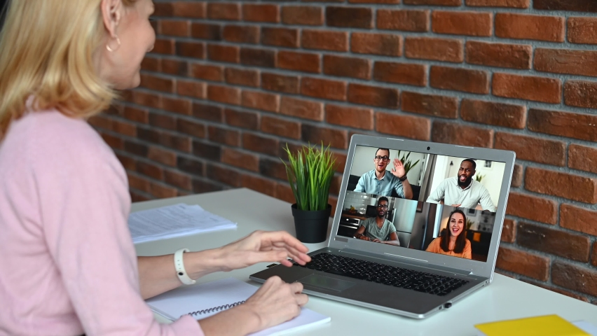 Back view a middle-aged business woman on virtual meeting with a diverse work team. A mid age female teacher, college professor conducts webinar, online lectures to group of multiracial students | Shutterstock HD Video #1066264966