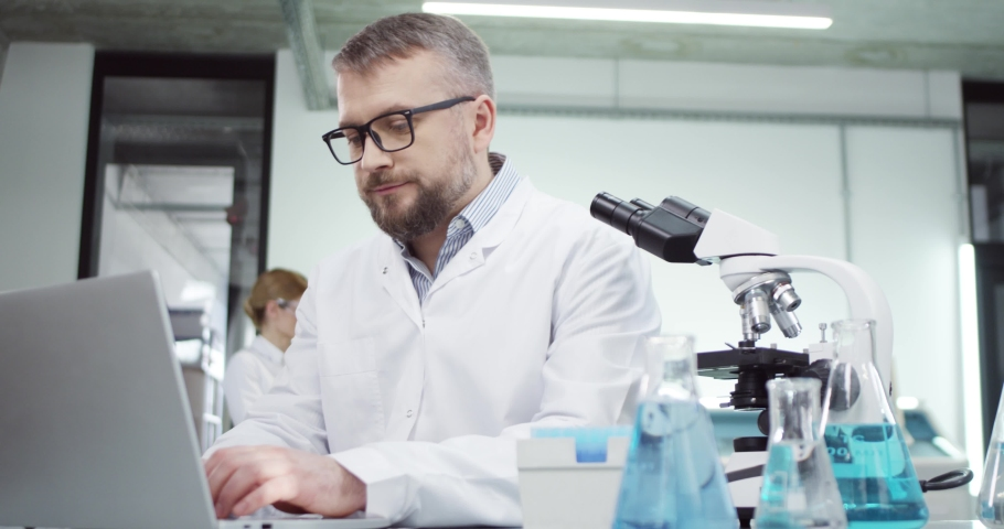 Portrait of happy middle-aged Caucasian male doctor laboratory scientist sitting in lab and texting browsing online on laptop, checking analysis and vaccine results, medical research, hospital concept Royalty-Free Stock Footage #1066267027