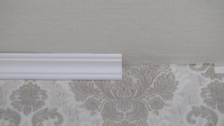 Installation of a ceiling skirting board on liquid nails to a ceiling, a wall. Royalty-Free Stock Footage #1066268395