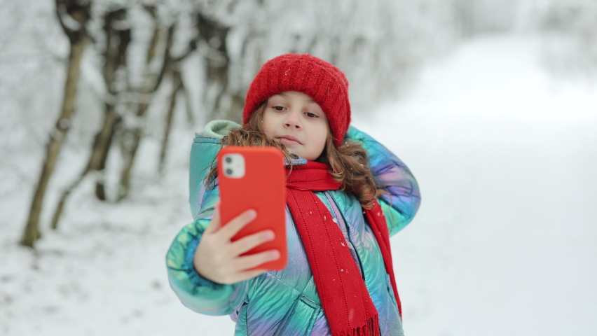 Cute little girl taking a selfie in the winter forest. Winter travel with children concept. Adorable happy smiling kid girl enjoy making selfie camera shot by smartphone. | Shutterstock HD Video #1066271173