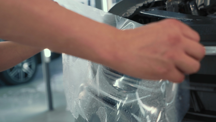 PPF or Paint Protection Film for cars or anti-gravel protection coating installing on headlight of new vehicle. Car detailing concept | Shutterstock HD Video #1066271365