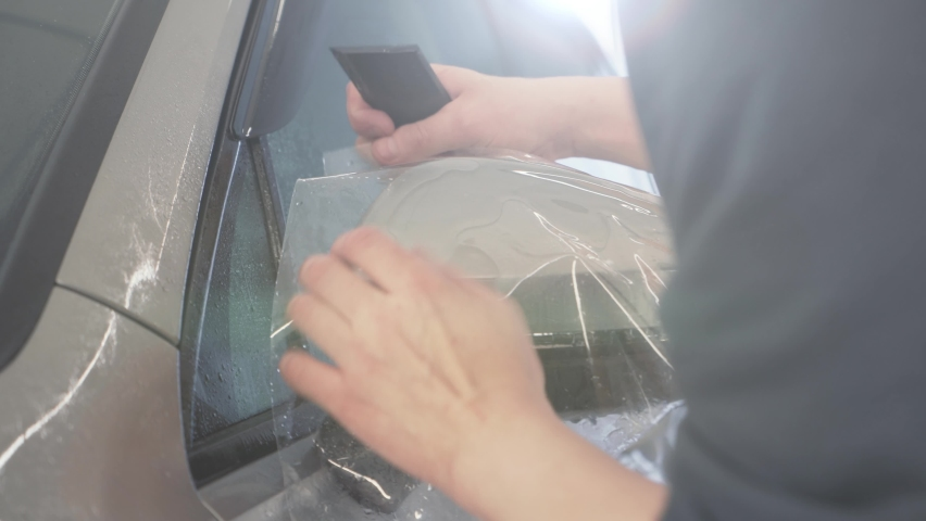 Workers hands wraps wet Paint Protection Film or anti-gravel protection coating on car mirror. Car detailing | Shutterstock HD Video #1066271368