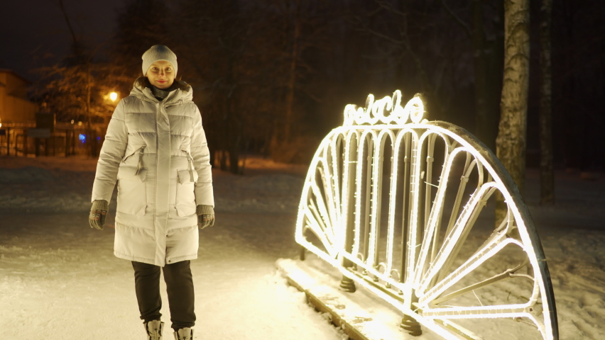Pregnant woman in winter near illuminated street Christmas lights in the evening smiling woman in warm jacket in snowy park | Shutterstock HD Video #1066274356