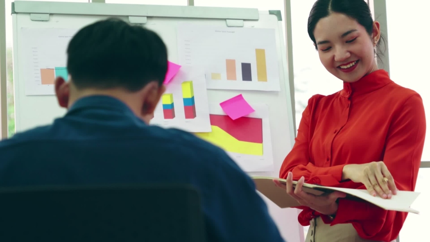 Young woman explains business data on white board in casual office room . The confident Asian businesswoman reports information progress of a business project to partner to determine market strategy . | Shutterstock HD Video #1066280737