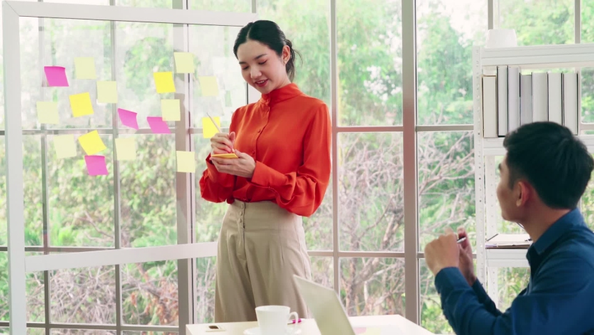 Business people work on project planning board in office and having conversation with coworker friend to analyze project development . They use sticky notes posted on glass wall to make it organized . | Shutterstock HD Video #1066280776