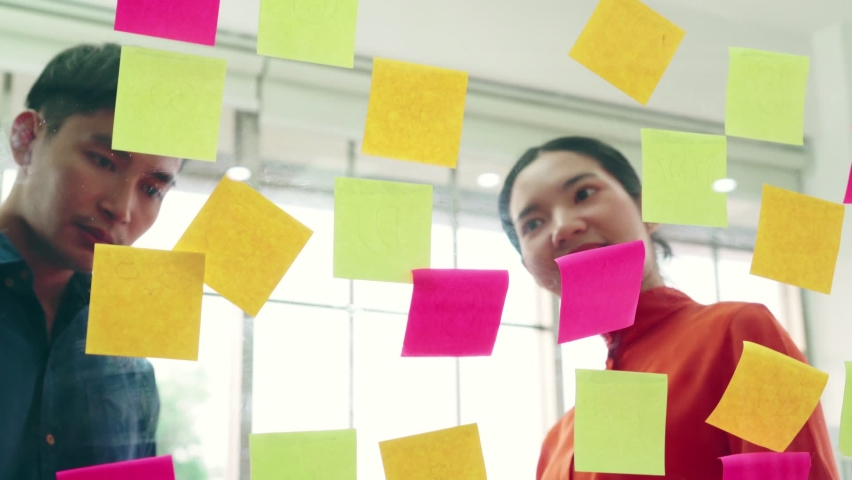 Business people work on project planning board in office and having conversation with coworker friend to analyze project development . They use sticky notes posted on glass wall to make it organized . | Shutterstock HD Video #1066280878