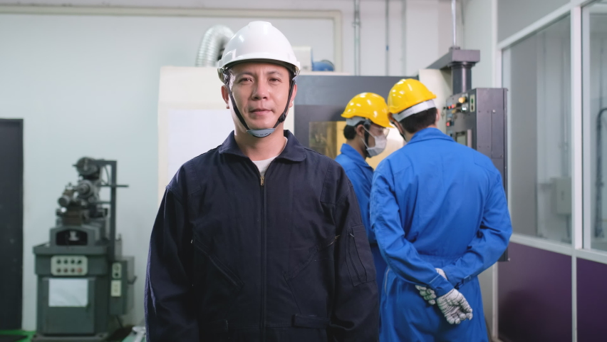 Factory worker wear mask and look at camera in front of his team working with machine in the back. Protection of infectius disease include Covid-19 during working in workplace. | Shutterstock HD Video #1066283605