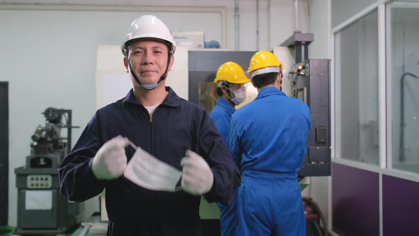 Factory worker take mask off and smile then look at camera in front of his team working with machine in the back. Protection of infectius disease include Covid-19 during working in workplace. | Shutterstock HD Video #1066283608