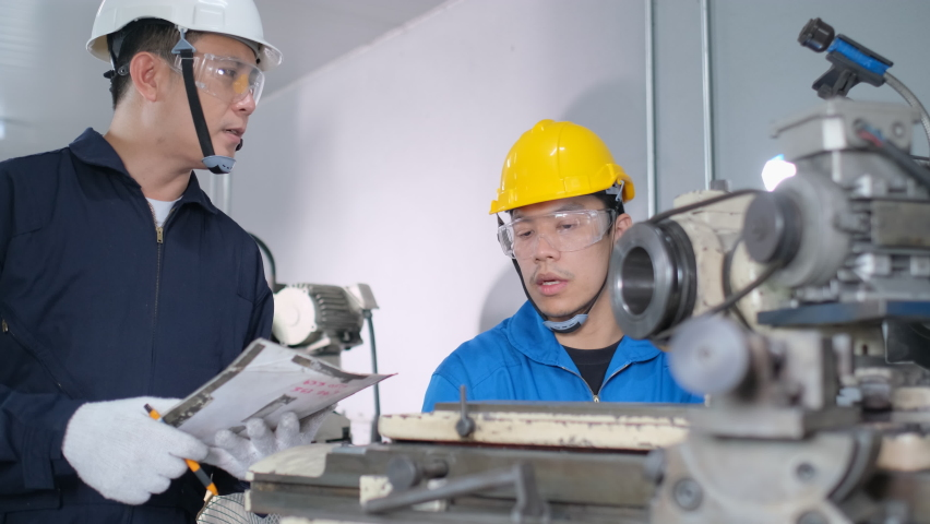 Two factory workers with protection uniform discuss and check the machine working in workplace. Teamwork and good system support industrial business concept. | Shutterstock HD Video #1066284490