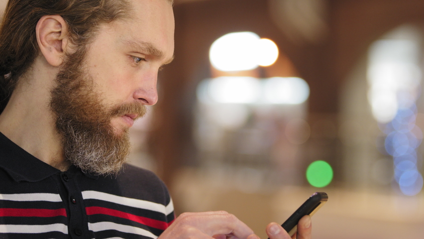 Side view of bearded young adult business man consumer using mobile phone to buy online chooses product surfing internet texting on social networks working looking at smartphone screen, close-up Royalty-Free Stock Footage #1066284661