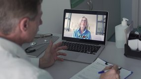 Older male doctor consulting senior old female patient by telemedicine online video call. Physician using telehealth medical chat virtual healthcare appointment on laptop computer. Over shoulder view