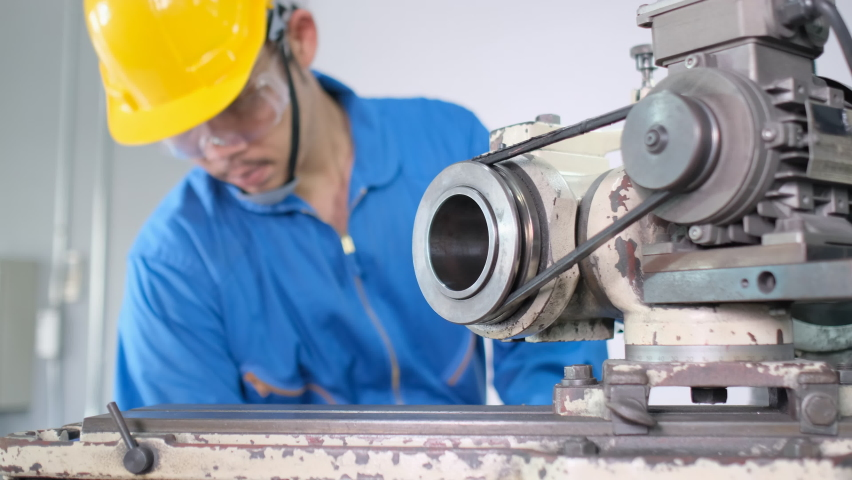 Close up Asian factory worker with yellow hardhat and blue uniform work with machine in workplace with maintenance and management for successful industrial concept. | Shutterstock HD Video #1066287616