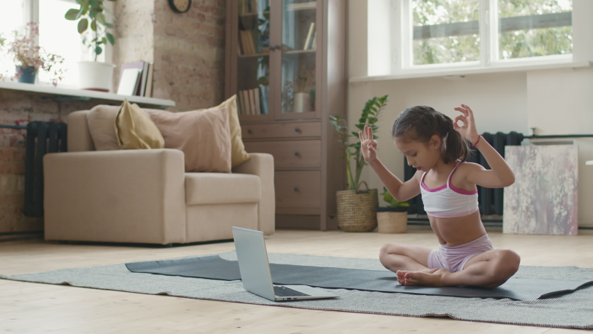 Tracking shot of cute little girl in sportswear sitting in Baddha Konasana pose on yoga mat and watching tutorial or online class on laptop | Shutterstock HD Video #1066296820