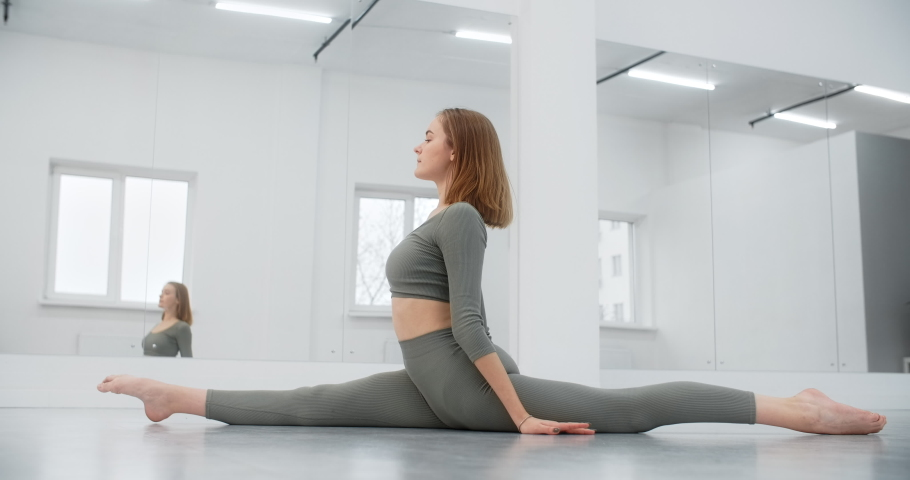Yoga instructor performs twine on the floor, gymnastic woman with tight body curves does pilates and stretching exercises on the floor of the white yoga place, yoga and pilates training, 4k 120p | Shutterstock HD Video #1066297360