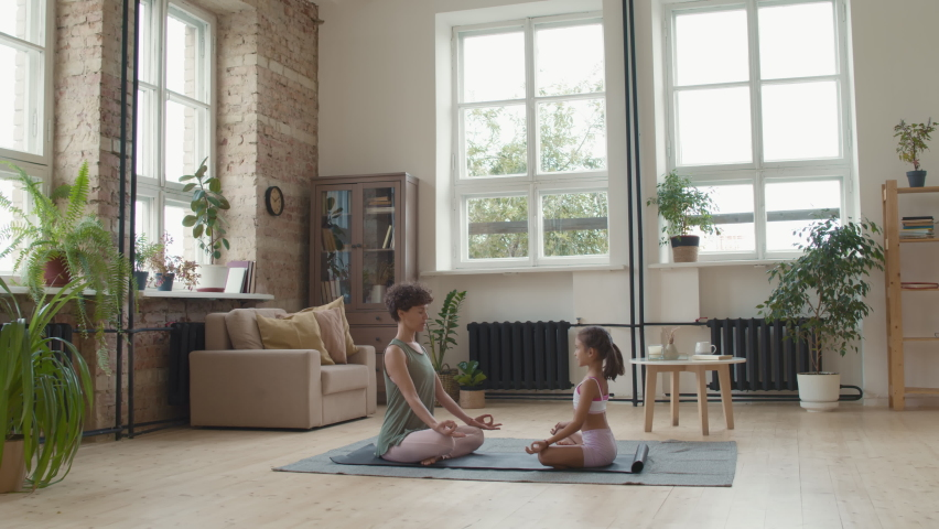 Wide shot of young woman and little girl in sportswear sitting together in lotus pose on mat and meditating in living room at home | Shutterstock HD Video #1066300075