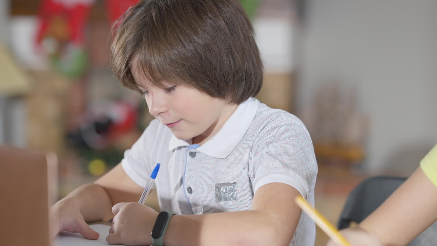 Portrait of charming brunette Caucasian schoolboy writing in workbook and talking to schoolgirl. Cute elementary students taking tests in classroom at school. Classmates chatting on exam. Royalty-Free Stock Footage #1066304800