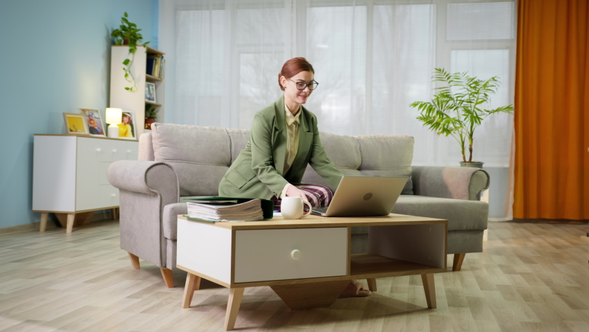 Work in quarantine, young female office worker in jacket and pajamas works remotely at home and runs with a cup of water in hands to notebook during video call sits on sofa in room | Shutterstock HD Video #1066314292