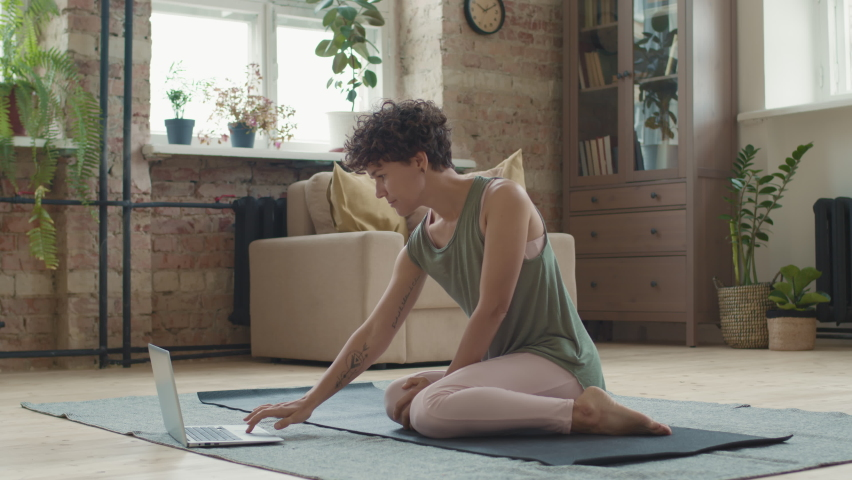 Tracking shot of fit young woman with short curly hair taking online yoga class. She is watching tutorial on laptop and doing cow face pose while sitting on mat in living room | Shutterstock HD Video #1066323961