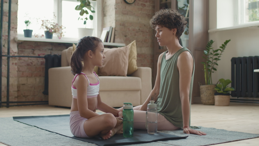 Slowmo tracking of cheerful young woman in sportswear sitting on floor in living room and chatting with little daughter after practicing yoga together, then looking at camera | Shutterstock HD Video #1066324183