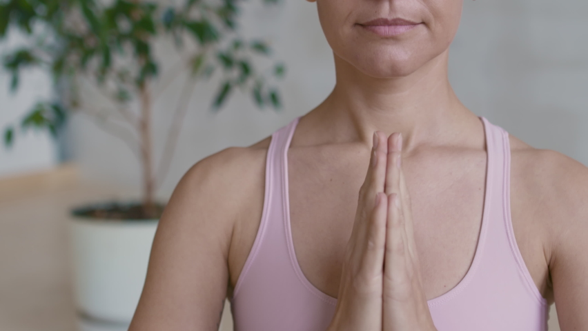 Close up tilt up portrait shot of young woman in pink sports bra meditating with her hands in praying position, then opening her eyes and looking at camera | Shutterstock HD Video #1066325377