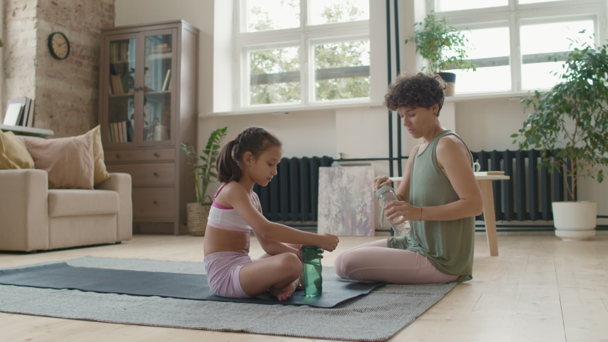 Tracking shot of cheerful young mother with short curly hair and her little daughter in sportswear drinking water and chatting while resting after practicing yoga | Shutterstock HD Video #1066326790