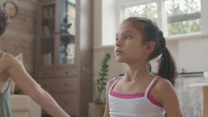 Slowmo tracking of little girl and her young mother in sportswear raising their arms and putting hands in praying pose while meditating at home | Shutterstock HD Video #1066326874