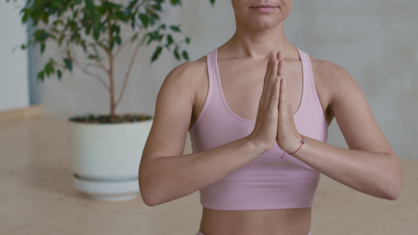 Mid-section close up of unrecognizable young woman in pink sports bra sitting in lotus pose and putting hands in praying position | Shutterstock HD Video #1066327228