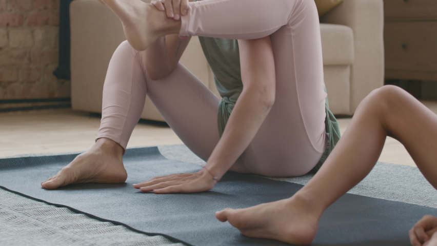Slowmo tracking shot of cheerful young mother and little daughter in sportswear doing firefly yoga pose on mat at home | Shutterstock HD Video #1066327960