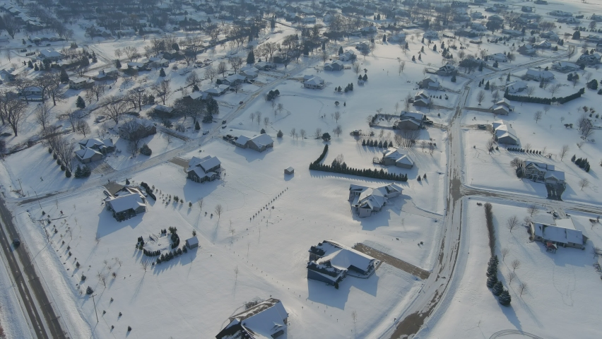 Flying over big houses with big yards in a suburban neighborhood right after a fresh snowfall snow.