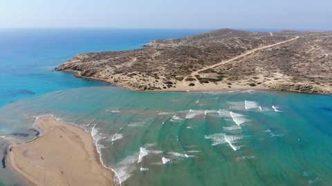 Scenic drone footage of Prasonisi peninsula in Rhodes in Greece surrounded by turquoise water. Kitesurfing and windsurfing. Waves on the Aegean Sea and calm flat water on the Mediterranean Sea.