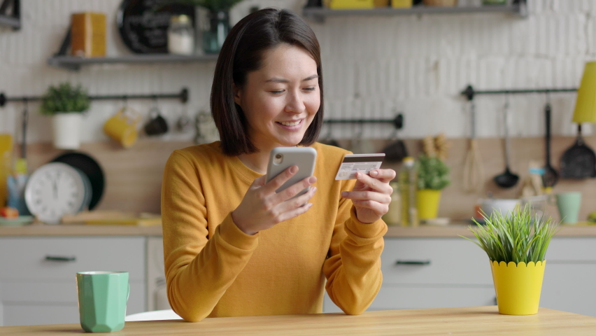 Multi ethnic female client holding banking credit card and smart phone using instant mobile payments. Happy mixed race asian customer shopper making purchase on smart phone e-banking service concept Royalty-Free Stock Footage #1066342585