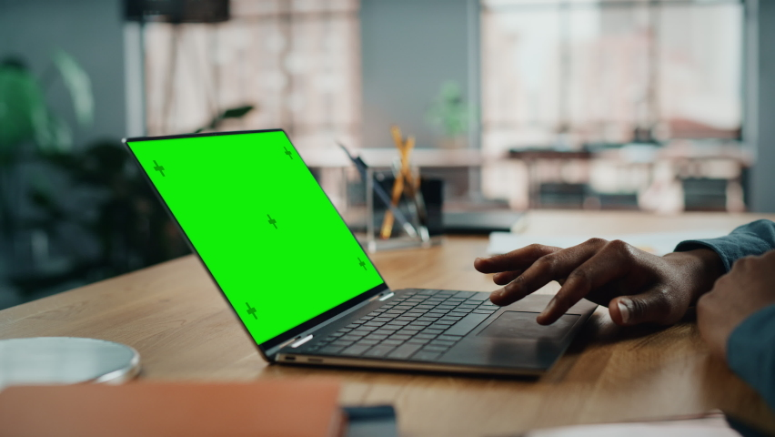 Close Up on Hands of Black African American Specialist Working on Laptop Computer with Green Screen Mock Up Display at Home Living Room. Freelance Man Chatting to Clients Over the Internet.