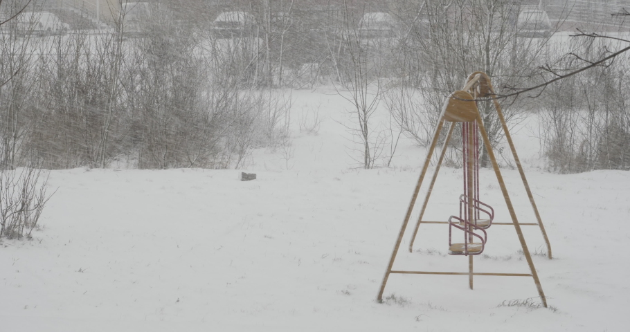 Winter Snow is Falling on an Street of an European City. Snowfall Cyclone. Winter in City, Blizzard. Snow Storm Against Background of Cars and Residential Buildings. Empty Playground Covered in Snow.
